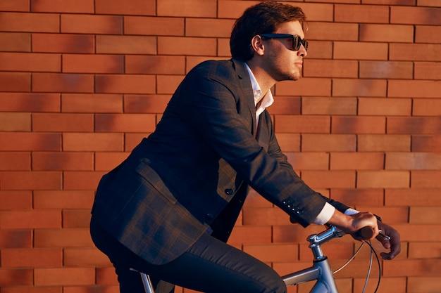 Bicicletta di guida sicura dell'uomo d'affari contro il muro di mattoni