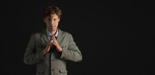 Fiducioso uomo d'affari o scienziato attende con le dita piegate. tagliare su sfondo nero. copia spase sul lato destro.