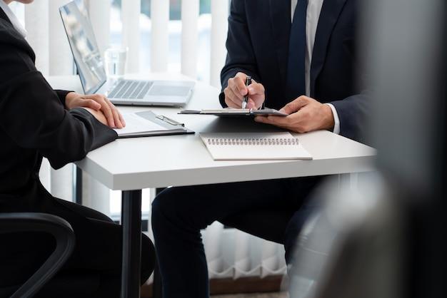 Fiducioso uomo d'affari seduto davanti a office manager parlare conducendo all'intervistatore
