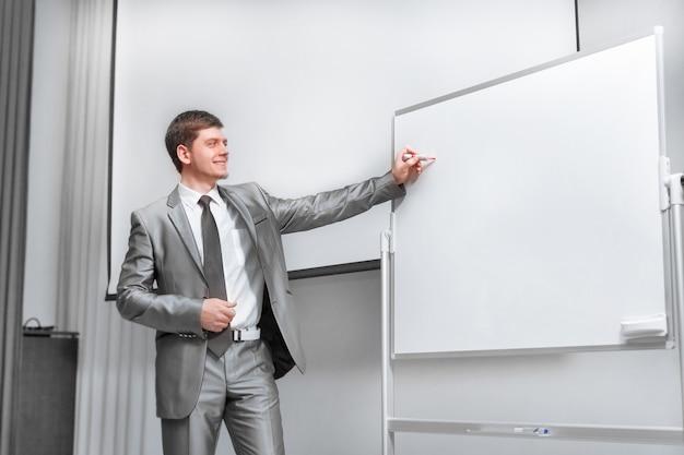 Fiducioso uomo d'affari in piedi sul palco nella sala conferenze. affari e istruzione