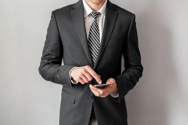Fiducioso imprenditore in tuta utilizza lo smartphone sul muro grigio