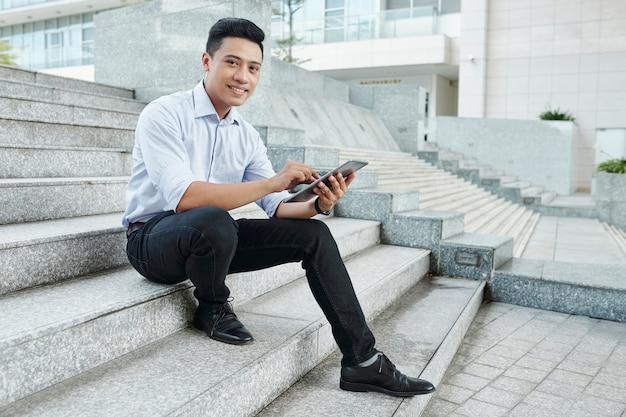 Fiducioso uomo d'affari con tavoletta digitale