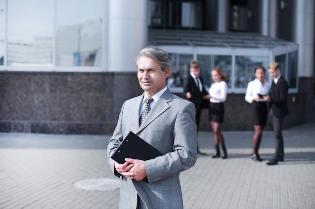 Fiducioso uomo d'affari con cartella, sul muro dell'edificio per uffici.