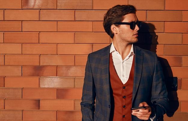 Fiducioso uomo d'affari con lo smartphone in piedi vicino al muro di mattoni