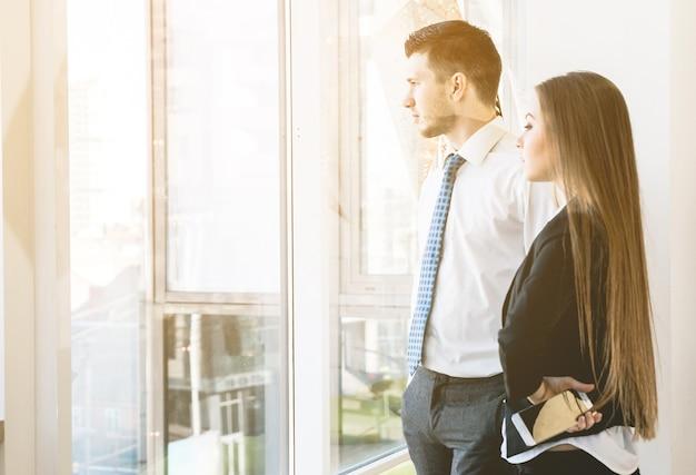 Fiduciosa donna d'affari mostra qualcosa in un lontano alle finestre sulla riunione dei colleghi. conversazione