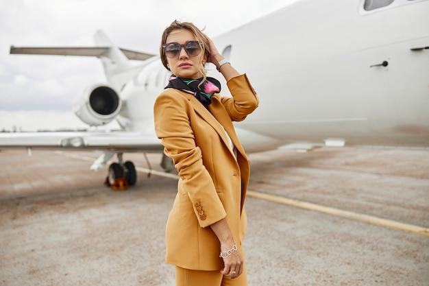 Fiduciosa donna d'affari in piedi sullo sfondo del jet dell'aeroplano. aereo passeggeri moderno. la donna indossa un abito formale e occhiali. giornata nuvolosa. aviazione civile commerciale. concetto di viaggio aereo e affari