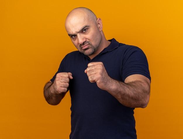 Fiducioso casual uomo di mezza età che fa gesto di boxe isolato su parete arancione