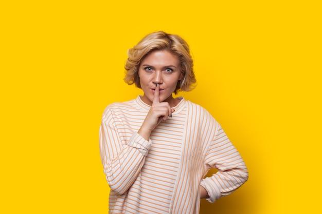 Fiduciosa donna caucasica con capelli biondi sta tenendo il dito alla bocca mentre posa su uno sfondo giallo