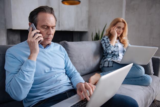 Fiducioso uomo anziano carismatico seduto a casa e utilizzando dispositivi moderni con la moglie durante la navigazione in internet e conversazioni di lavoro