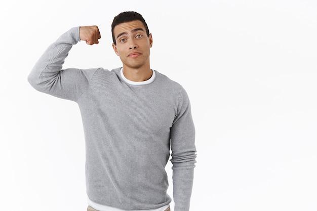 Giovane uomo atletico ispanico sicuro e sfacciato, che si vanta della forza del corpo