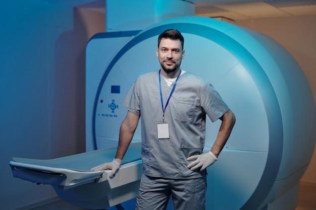 Medico fiducioso in uniforme grigia in piedi accanto al tavolo dell'attrezzatura per la risonanza magnetica