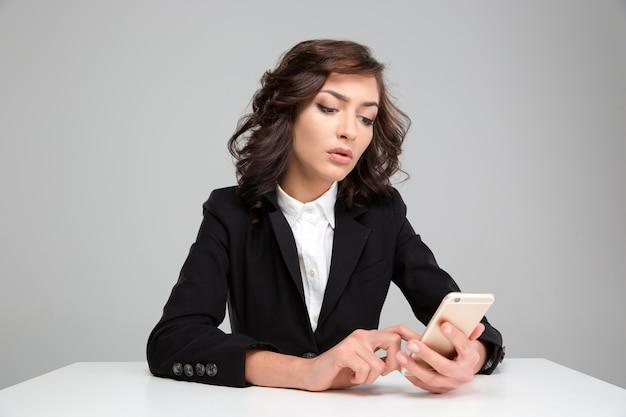 Bella giovane donna riccia concentrata sicura in giacca nera che si siede e che usa il cellulare