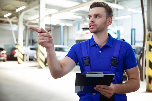 Fiducioso e concentrato, uno specialista di riparazioni auto giovane ed esperto con un tablet in mano ispeziona e diagnostica l'auto per guasti