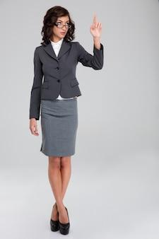 Fiduciosa donna d'affari riccia graziosa in occhiali e abito grigio che tocca copyspace con un dito e in piedi con le gambe incrociate