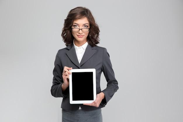 Fiduciosa giovane donna riccia in giacca grigia e occhiali che mostra lo schermo del computer tablet vuoto