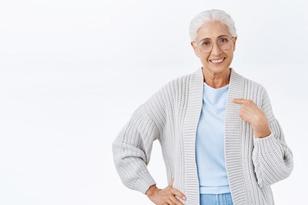 Donna anziana sicura e determinata con i capelli grigi pettinati con gli occhiali, indicandosi, sorridendo sicura di sé, facendo domanda per un lavoro come bambinaia, motivata e senza dubbi che sia la migliore, muro bianco