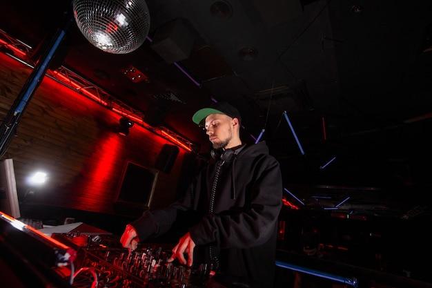 Fiducioso dj uomo mescolando la migliore traccia in discoteca alla festa. concetto di vita notturna. palla da discoteca. attrezzatura musicale professionale.