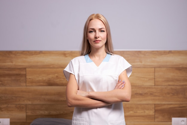 Donna sicura del medico o infermiera che posa nell'usura whitemedical, concetto di sanità. donna bionda sta con le braccia conserte isolate nella stanza d'ospedale