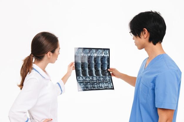 Medici fiduciosi coppia indossando uniforme in piedi isolato sopra il muro bianco, esaminando la fotografia a raggi x
