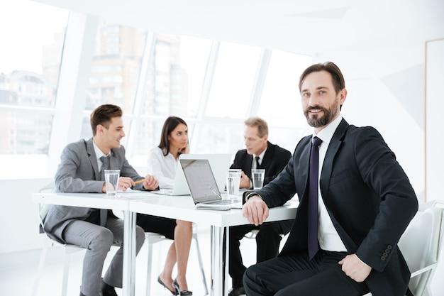 Fiducioso uomo d'affari anziano seduto al tavolo con partner commerciali e laptop