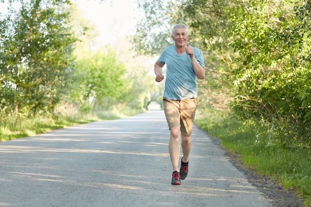 Il corridore maschio anziano sicuro corre sulla strada, ha allenamento di mattina, essendo molto attivo, gode della bella natura, essendo in pensione. il pensionato ha un allenamento all'aperto da solo. concetto di sport e motivazione