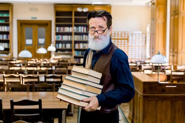 Fiducioso ed elegante bibliotecario del professore universitario insegnante, indossando abiti eleganti, felice di condividere conoscenze, con in mano una pila di libri diversi, in piedi in una biblioteca vintage al chiuso.