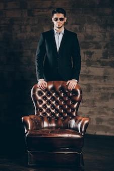 Fiducioso ed elegante. giovane bell'uomo in giacca e occhiali da sole appoggiato su una sedia di pelle e guardando la telecamera mentre si trova in piedi su sfondo grigio scuro