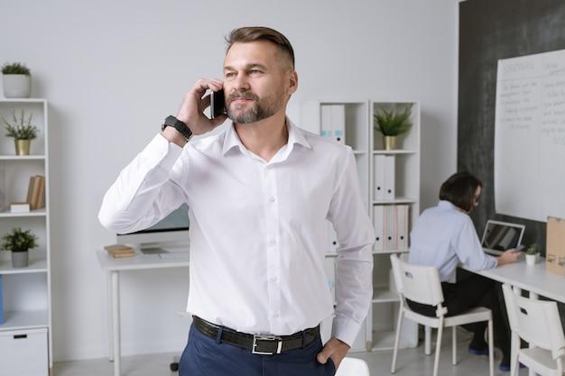 Imprenditore fiducioso con smartphone che consulta uno dei suoi dipendenti mentre si trovava in ufficio