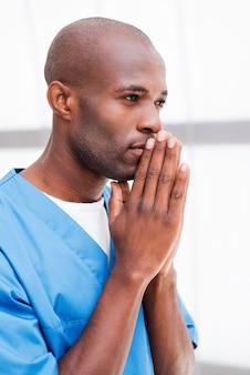 Chirurgo sicuro ed esperto. vista laterale del premuroso giovane medico africano in uniforme blu che tiene le mani giunte vicino al viso e guarda lontano e tiene le braccia incrociate