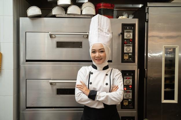 Fiducioso chef musulmano femminile sorride alla telecamera e ha incrociato il braccio nella cucina del ristorante