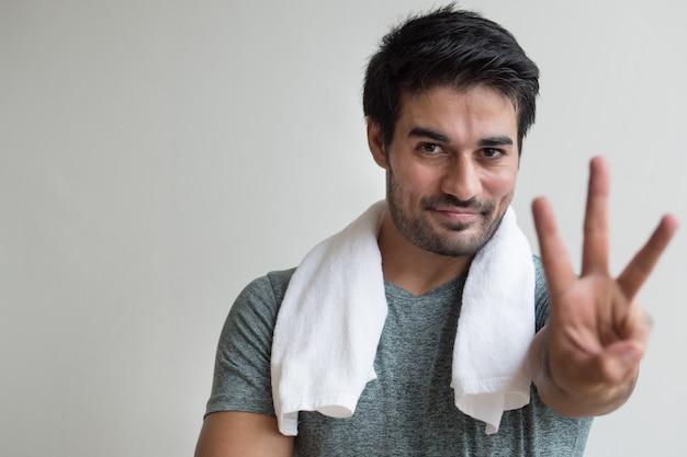 Uomo sicuro di forma fisica che indica su tre dita; ritratto dell'uomo asiatico di forma fisica felice, sano, fiducioso, amichevole che indica il segno del dito numero 3 o il gesto della mano; modello uomo adulto asiatico nord indiano