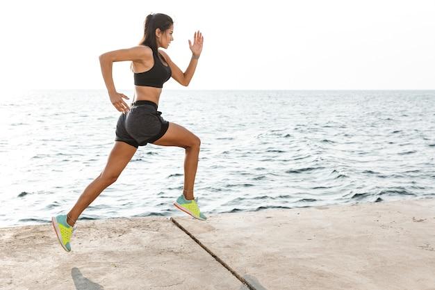 Fiducioso fitness donna che indossa abiti sportivi in esecuzione in spiaggia