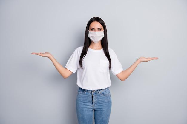 Fiducioso ragazza promotore tenere la mano dimostrare sicurezza covid29 prevenzione prodotto opzione misura confrontare indossare maschera medica tshirt jeans denim isolato su sfondo di colore grigio