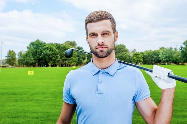 Giocatore di golf sicuro. fiducioso giovane giocatore di golf maschio che tiene il conducente e guarda la telecamera mentre si sta in piedi sul green