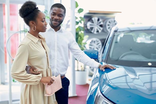 Fiducioso bell'uomo afro mostra alla moglie un'auto che gli piace, guardano l'auto e discutono