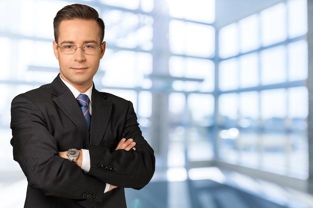 Fiducioso bell'uomo d'affari con le braccia in tasca sullo sfondo
