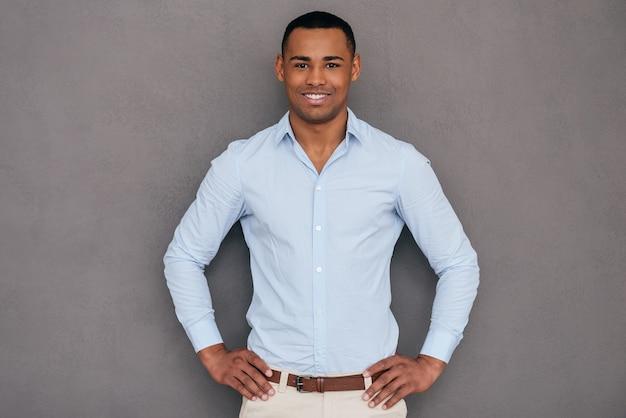 Fiducioso e bello. fiducioso giovane africano che tiene le braccia incrociate e