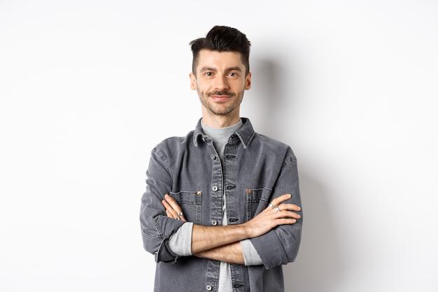 Fiducioso bel ragazzo in abito casual braccia incrociate sul petto, sorridendo compiaciuto, in piedi professionale su sfondo bianco.