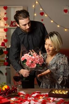 Fiducioso bell'uomo che dà un mazzo di fiori e guarda una bella donna sorpresa seduta al tavolo in soggiorno il giorno di san valentino Foto Premium