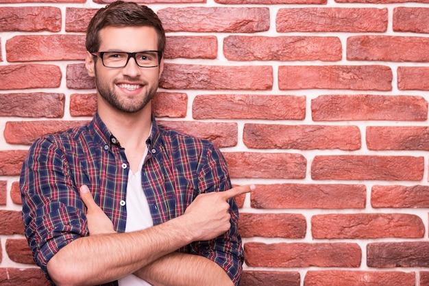 Bello fiducioso che indica la tua pubblicità. bel giovane che tiene le braccia incrociate e indica lo spazio della copia mentre si trova contro un muro di mattoni