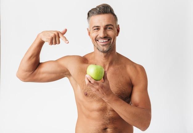 Fiducioso bell'uomo senza camicia in piedi isolato su bianco, flettendo i bicipiti, mostrando mela verde