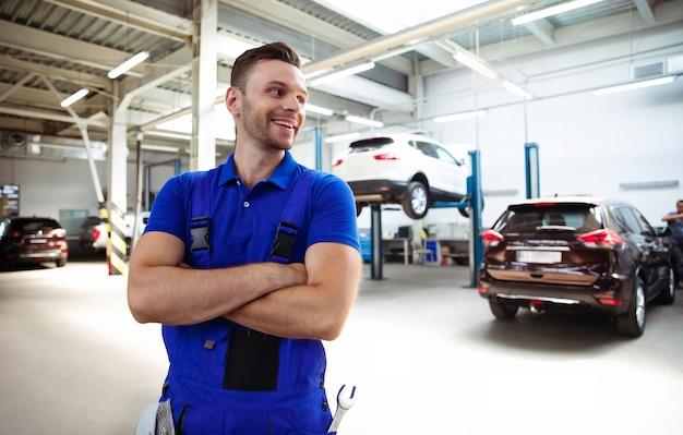 Fiducioso bel giovane ed esperto riparatore di auto in tute da lavoro in posa sullo sfondo di auto sollevate in un servizio di auto