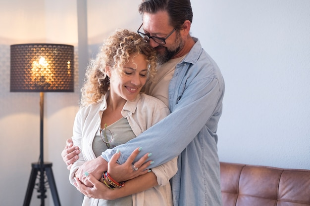 Gli adulti fiduciosi e felici si divertono a casa insieme abbracciandosi e amando con cura e romanticismo
