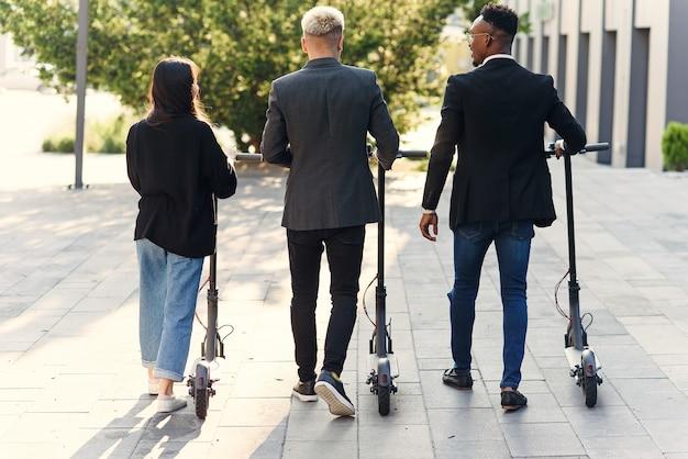 I colleghi dell'ufficio multirazziale felici fiduciosi che discutono del progetto di affari si avvicinano all'edificio per uffici con scooter elettrici