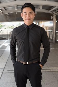 Uomo d'affari asiatico sicuro, felice, di successo