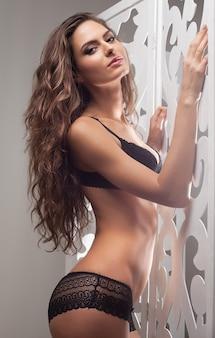Fiducioso nella sua bellezza. attraente giovane donna in lingerie nera in posa e guardando la telecamera