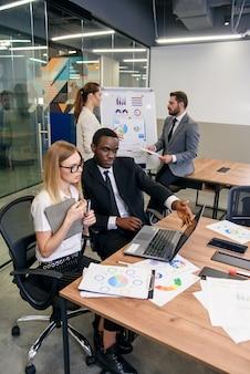Squadra multietnica professionale di grande spirito fiducioso che lavora insieme a un progetto commerciale congiunto nella sala riunioni utilizzando laptop e report.