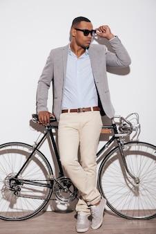 Fiducioso nel suo stile perfetto. integrale del giovane africano sicuro che regola i suoi occhiali da sole