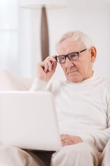 Fiducioso lavoratore a domicilio. bell'uomo anziano che lavora al computer portatile mentre è seduto su una sedia nel suo appartamento