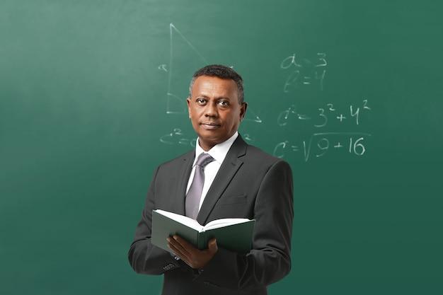 Fiducioso insegnante indiano in piedi vicino alla lavagna